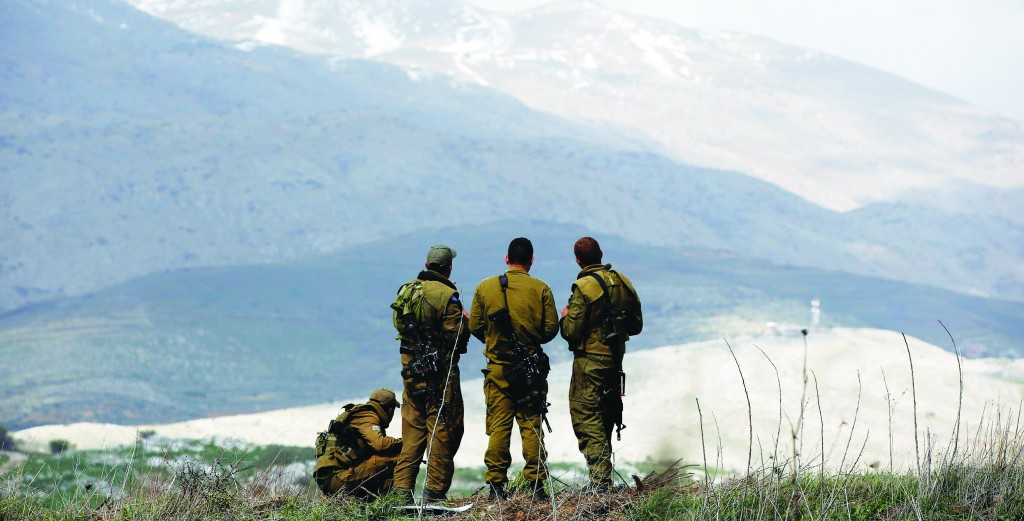 Israeli soldiers stand in the Golan Heights overlooking Syria March 19, 2014. (REUTERS/Ronen Zvulun)