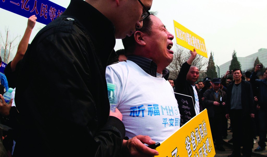 Wen Wanchang, whose son was on board the missing Malaysia plane, holds a placard Tuesday as he protests outside the Malaysian embassy in Beijing. (AP Photo/Ng Han Guan)