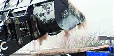 A backhoe pours salt onto a pile ahead of a snowstorm.