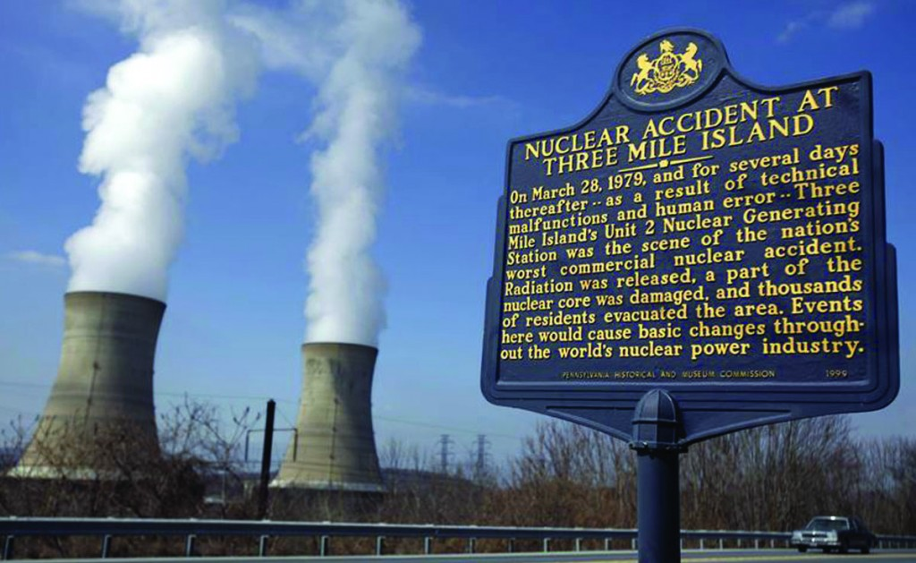 A historic marker stands near the Three Mile Island Unit 2 reactor, site of the March 28, 1979, nuclear accident, as steam pours from the cooling towers of the TMI Unit 1 plant. (CAROLYN KASTER / AP)