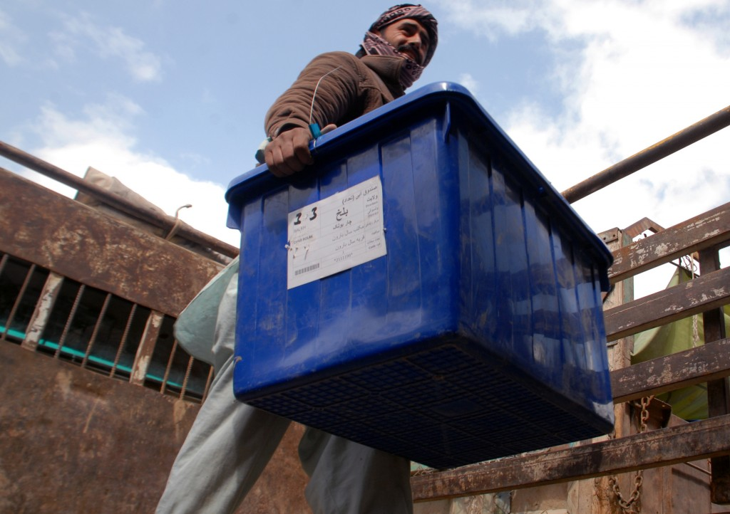 An Afghan election worker carries out a ballot box from a truck at a warehouse of the Independent Elections Commission in Mazar-i-Sharif, capital of the Balkh province, Afghanistan, Sunday, April 6, 2014. (AP Photo/Mustafa Najafizada)