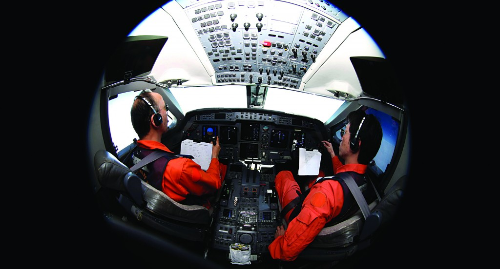 Pilots Makoto Hoshi (L) and Shunichi Yumiza look at notes as they sit in the cockpit of the Japan Coast Guard Gulfstream V aircraft as it flies over the southern Indian Ocean looking for debris from missing Malaysian Airlines flight MH370 Tuesday. (REUTERS/Rob Griffith/Pool)