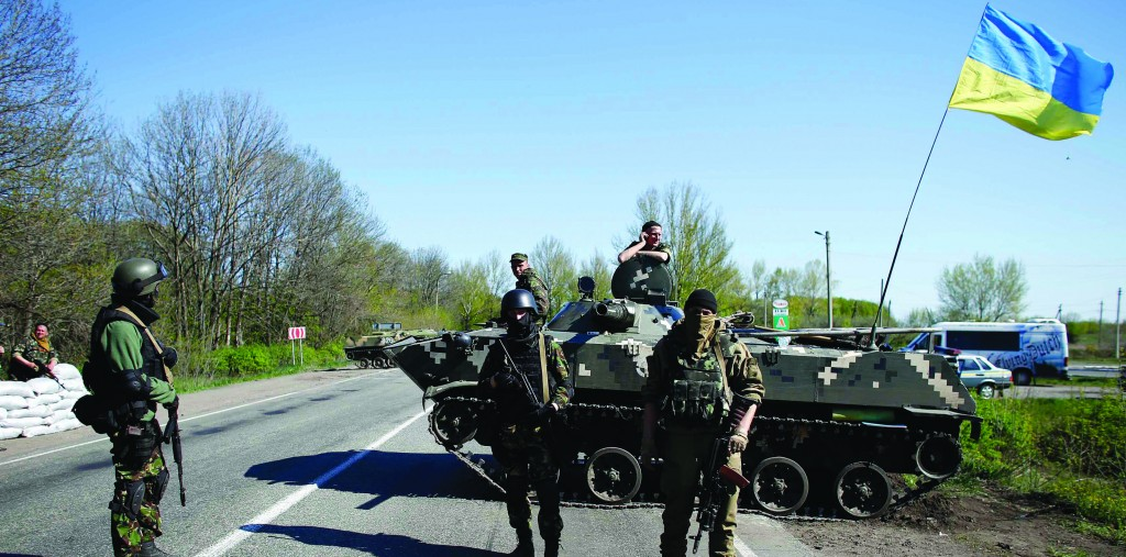 Ukrainian soldiers stand guard in front of an armored personnel carrier at a checkpoint in the village of Malinivka, east of Slaviansk in eastern Ukraine Thursday. (REUTERS/Marko Djurica)