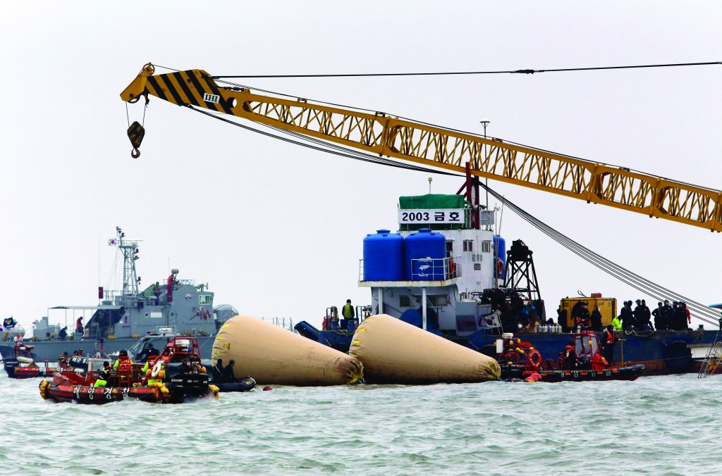 Searchers and divers look for people believed to have been trapped in the sunken ferry Sewol near buoys which were installed to mark the vessel in the water off the southern coast near Jindo, south of Seoul, South Korea, Tuesday.  (AP Photo/Lee Jin-man)