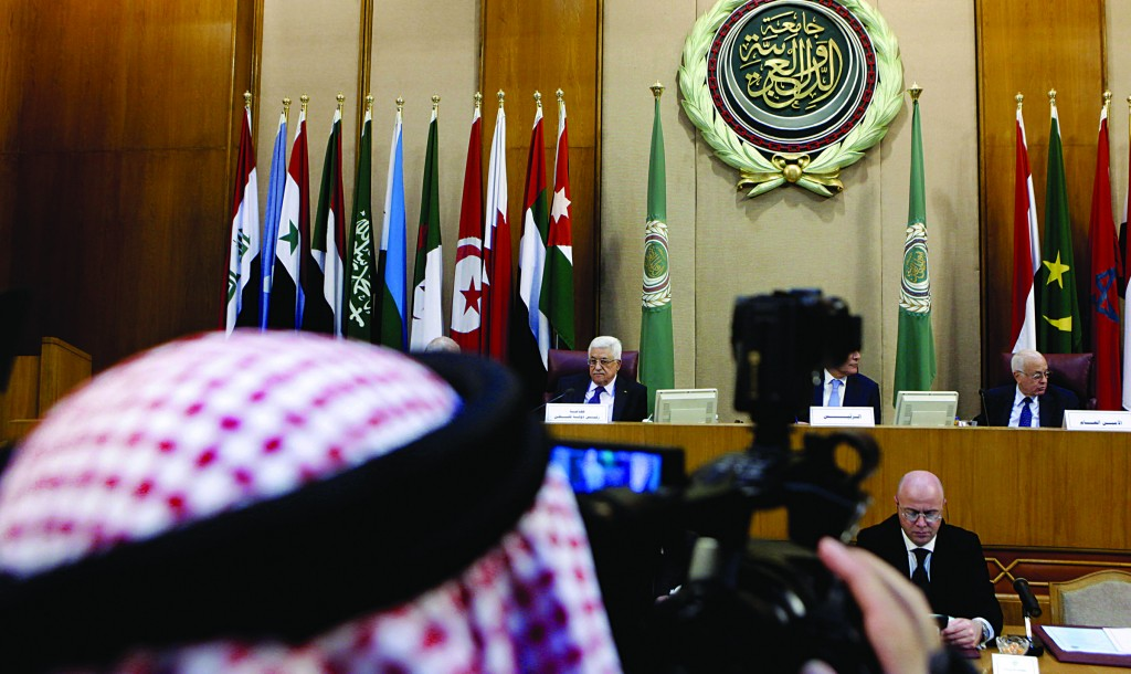A Kuwaiti cameraman films the meeting of Palestinian President Mahmoud Abbas, center left, with Arab foreign ministers at the League's headquarters in Cairo, Egypt. Arab League Secretary-General Nabil Elaraby, at top right. (AP Photo/Amr Nabil)