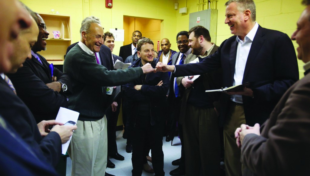Mayor Bill de Blasio fist-bumps Sen. Charles Schumer after a Sandy-related press conference in Queens Saturday. (Rob Bennett/City Hall)