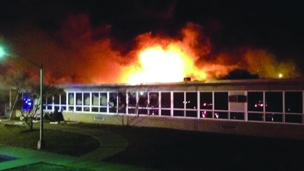 Flames burn down the James Monroe School in Edison Township, N.J., on March 22, a blaze blamed on a cigarette discarded by the janitor. (AP Photo/Home News Tribune, Suzanne Russell)