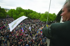 A Pro-Russian activist waves a Donbas Republic flag over a crowd celebrating the capture of an administration building in the center of Luhansk, Ukraine, one of the largest cities in Ukraine's troubled east, Tuesday. (AP Photo/Alexander Zemlianichenko)