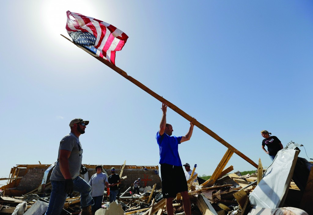Justin Shaw, left, helps Nick Conway raise a flagpole at his home that was destroyed by a tornado, Monday, in Vilonia, Ark. (AP Photo/Eric Gay)
