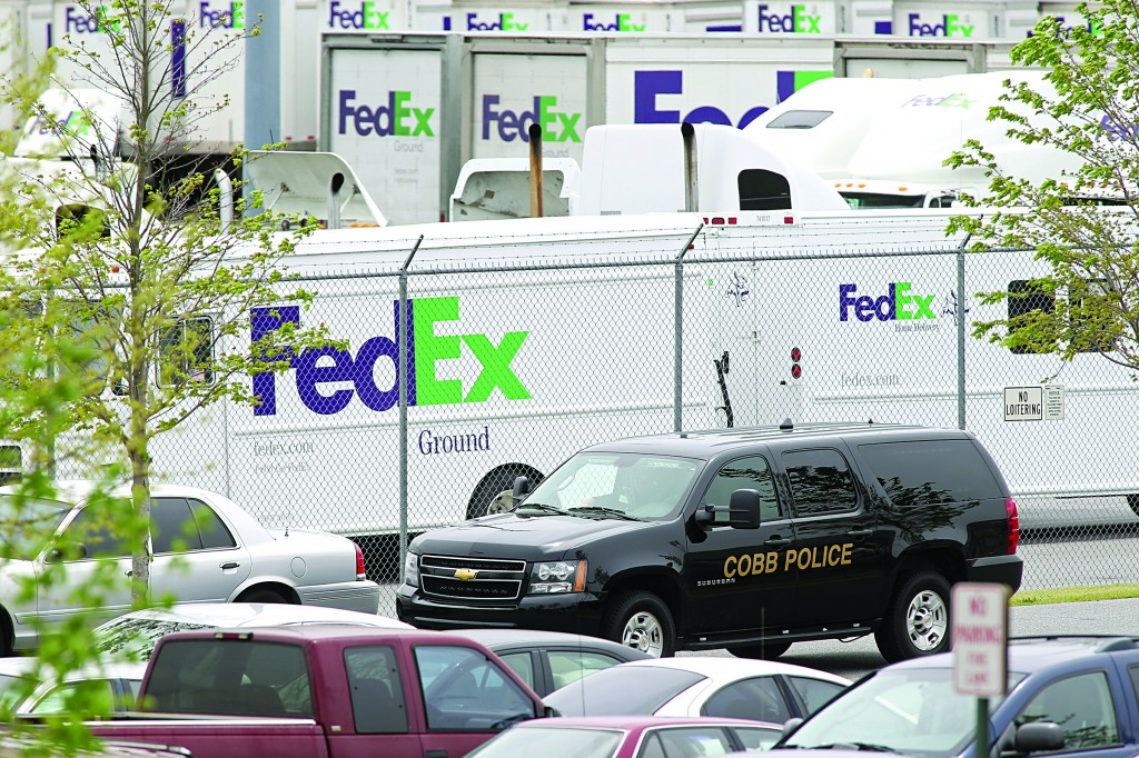 A Cobb County Police automobile drives by FedEx trucks after an early morning shooting at the Airport Road FedEx facility Tuesday, in Kennesaw, Ga.  (AP Photo/Jason Getz)