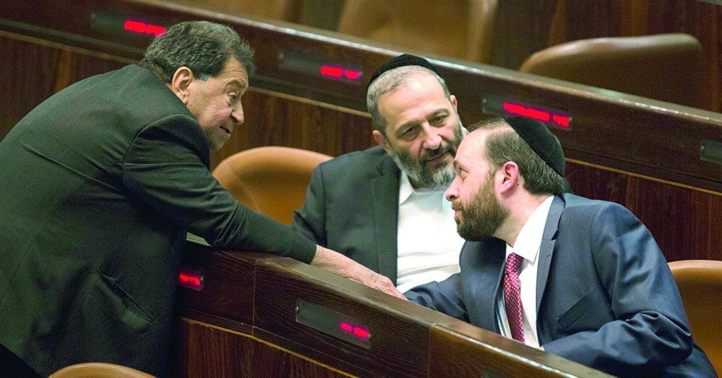 Shas chairman Aryeh Deri (C) talking with Shas MK Ariel Atias (R) and Labor MK Binyamin Ben Eliezer during a special Knesset session on Monday. (Flash90)