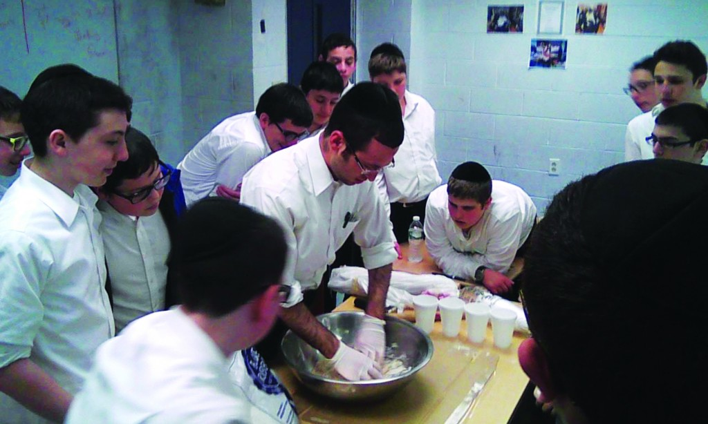 Rabbi Nachum Chaim Srebro, assistant Menahel of the mechinah at Yeshiva Darchei Torah, demonstrating how to knead and roll dough for matzah in preparation for the students going to bake matzos in Brooklyn on Wednesday.
