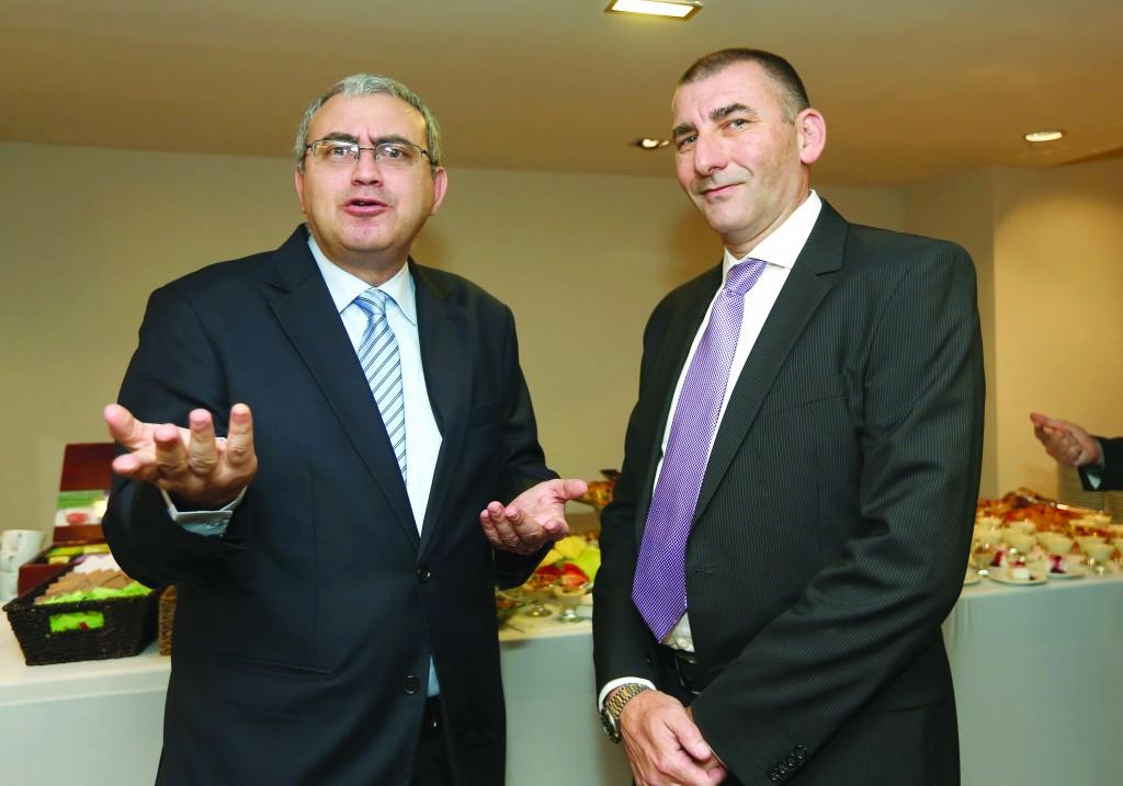 Director general of Israel Post, Haim Almoznino (left), with Postal Bank director Yoel Naveh.  (Moshe Shai/FLASH90 )