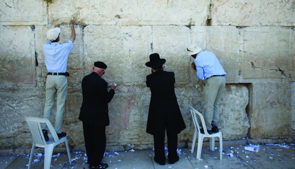 Rav of the Kosel Rabbi Shmuel Rabinovitz (2nd R) and workers remove notes from the cracks of the Wall ahead of Pesach. (REUTERS/Ronen Zvulun)