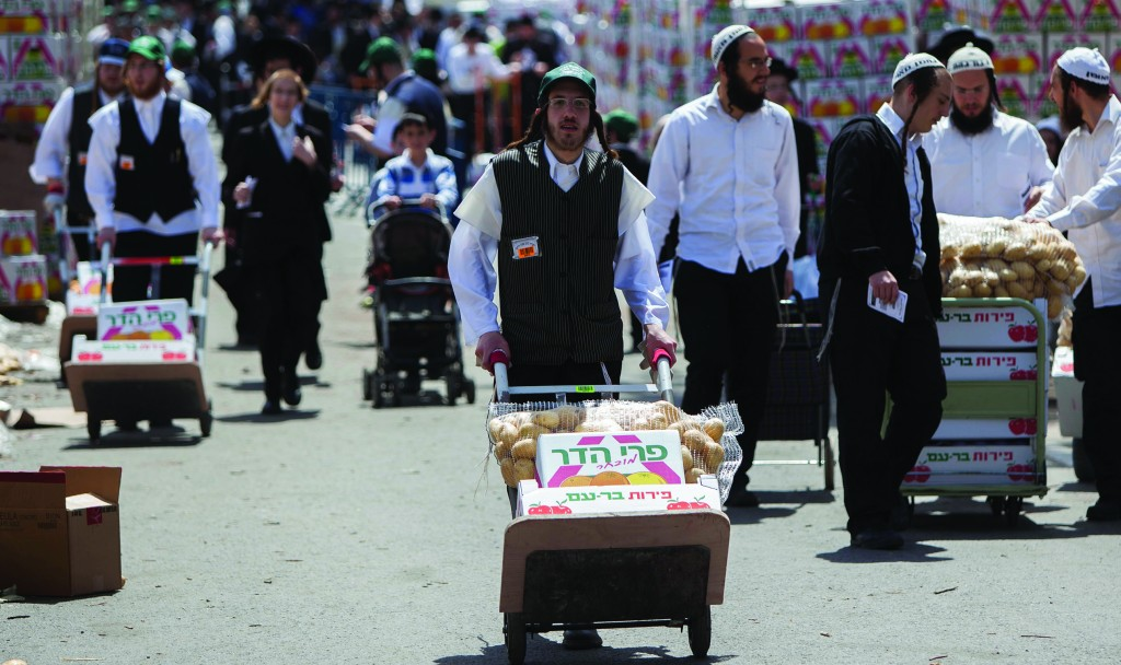 (L-R) Carrying food products for distribution to needy families, in Meah Shearim on Wednesday. (Yonatan Sindel/Flash90)