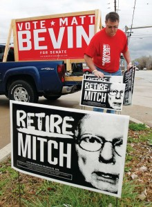 Campaign volunteer Chris Gallaher places signs near a road during a Honk and Wave event for Republican senate candidate Matt Bevin in Louisville, Kentucky. (REUTERS/John Sommers II)