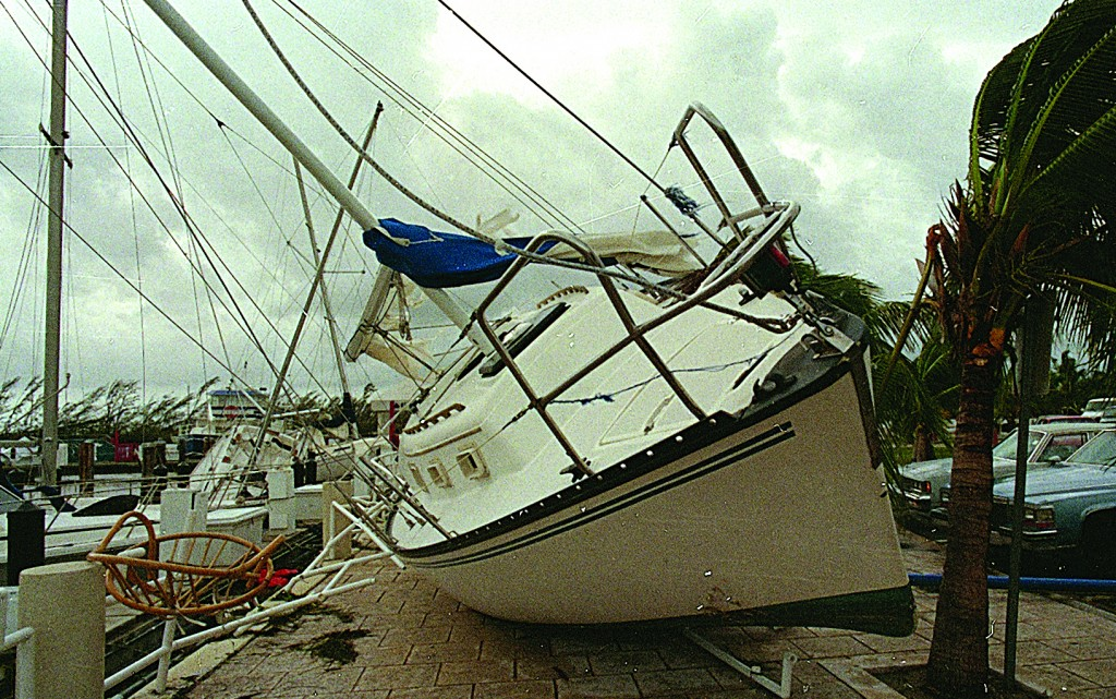 In this Aug. 24, 1992 file photo, a sailboat sits on a sidewalk at Dinner Key in Miami after it was washed ashore by Hurricane Andrew.  (AP Photo/Terry Renna, File)