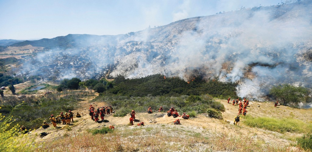 Firefighters move back down the embankment to the brush fire Thursday, in San Marcos, Calif. (AP Photo)