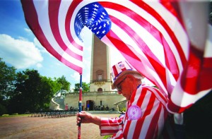 A breeze billows the American flag over the head of Tommy Sammons of Richmond, Va., as he waits for a military band concert to begin at the Carillon, a memorial dedicated to Americans who died in World War I in Richmond, Va. on Monday. Sammons, a U.S. Navy veteran, is a fixture at patriotic festivities in Richmond, typically dressing as Uncle Sam and carrying a flag.  (AP Photo/ Richmond Times-Dispatch, Dean Hoffmeyer)