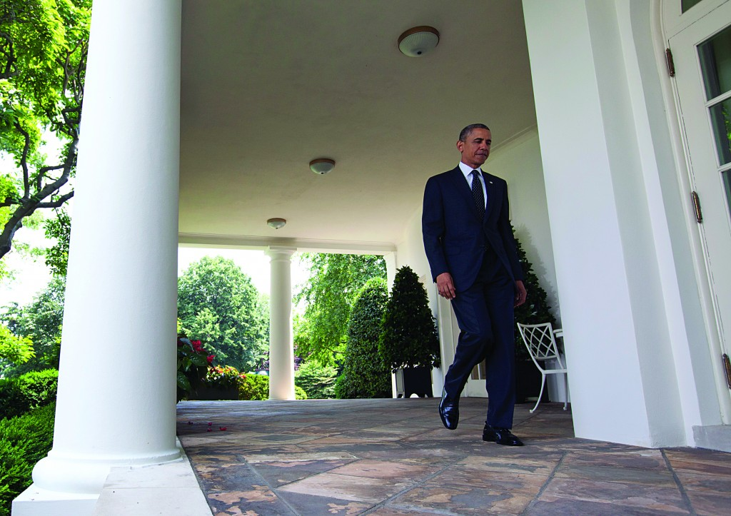 President Barack Obama walks from the Oval Office to speak about Afghanistan, Tuesday, in the Rose Garden of the White House in Washington. (AP Photo/Carolyn Kaster)