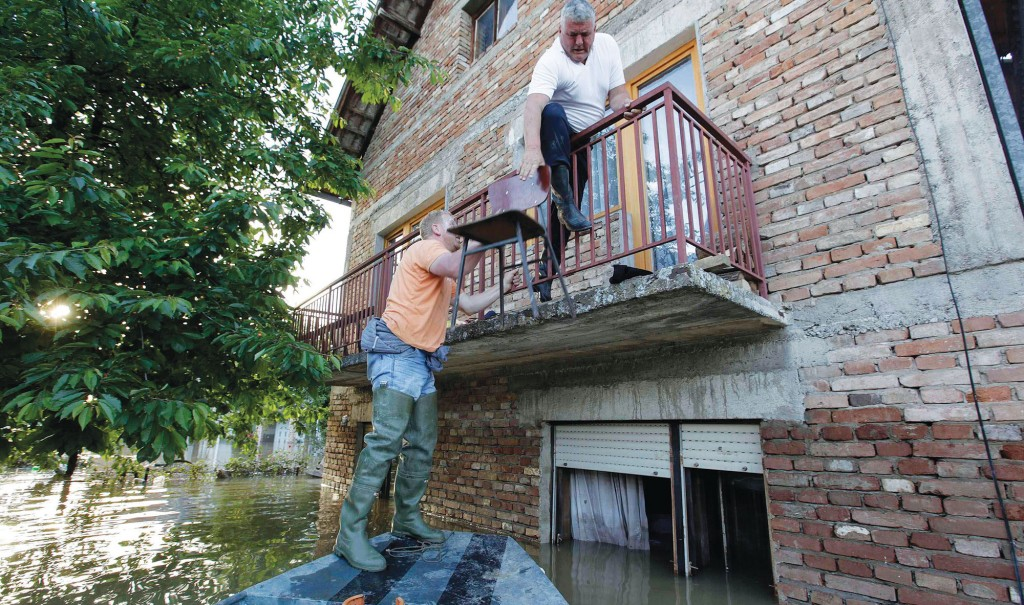 """A man climbs on the balcony of his house during heavy floods in Bosanski Samac Monday. Bosnia said on Monday that more than a quarter of its 4 million people had been affected by the worst floods to hit the Balkans in living memory, comparing the """"terrifying"""" destruction to that of the country's 1992-95 war. (REUTERS/Srdjan Zivulovic)"""