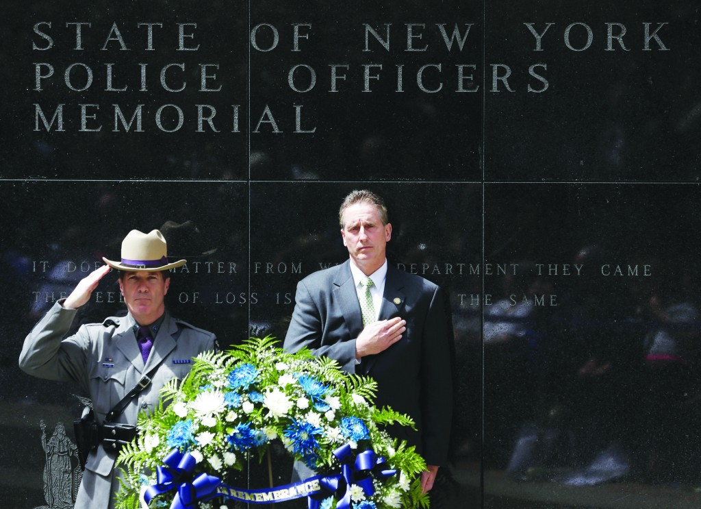 Trooper William Gannon of the New York State Police and Lt. Gov. Robert Duffy stand behind a wreath after placing it at the State of New York Police Officers Memorial on Tuesday, in Albany, N.Y.  (AP Photo/Mike Groll )
