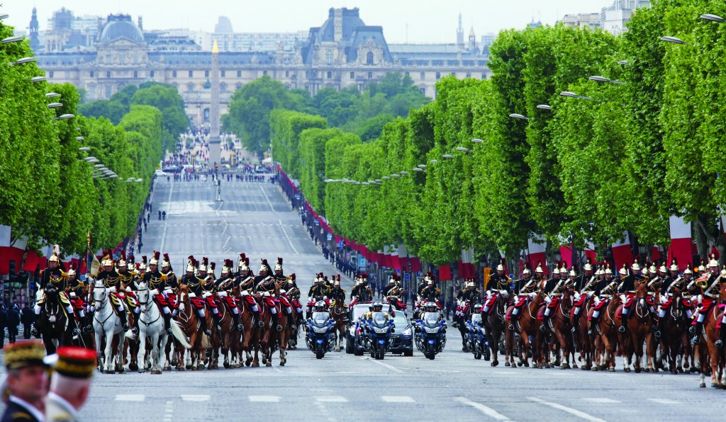 A motorcade escorting French President Francois Hollande rides up the Champs Elysees in Paris Thursday, before a ceremony at the Arc de Triomphe marking the 69th anniversary of the end of World War II.  (AP Photo/Remy de la Mauviniere/Pool)