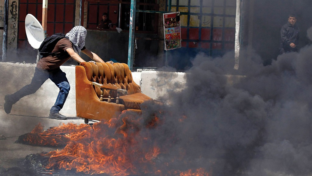 A Palestinian pushes a sofa into a fire during clashes with Israeli troops in rioting at Qalandia checkpoint near Ramallah on Thursday. (REUTERS/Ammar Awad)