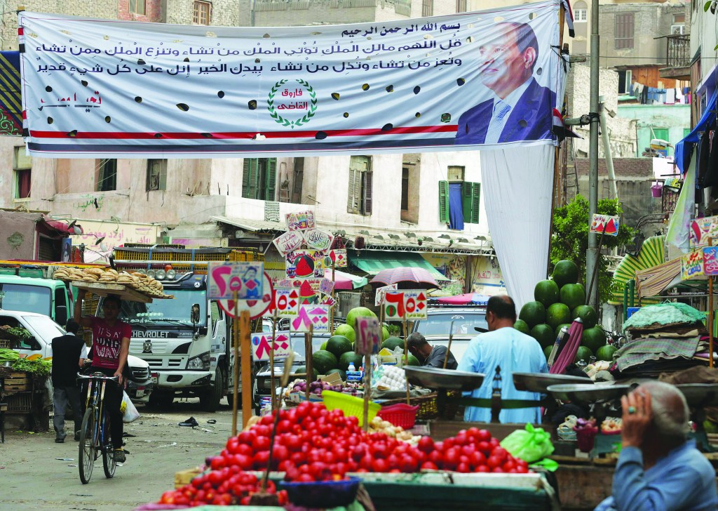 People walk in a market near an electoral banner for presidential candidate Abdel Fattah al-Sisi in Cairo, Wednesday.  (REUTERS/Asmaa Waguih)