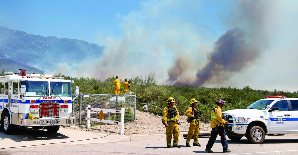 Smoke from the Etiwanda Fire looms behind firefighters staging on Wilson Avenue in Rancho Cucamonga, Calif. (AP Photo/San Gabriel Valley Tribune, Leo Jarzomb)