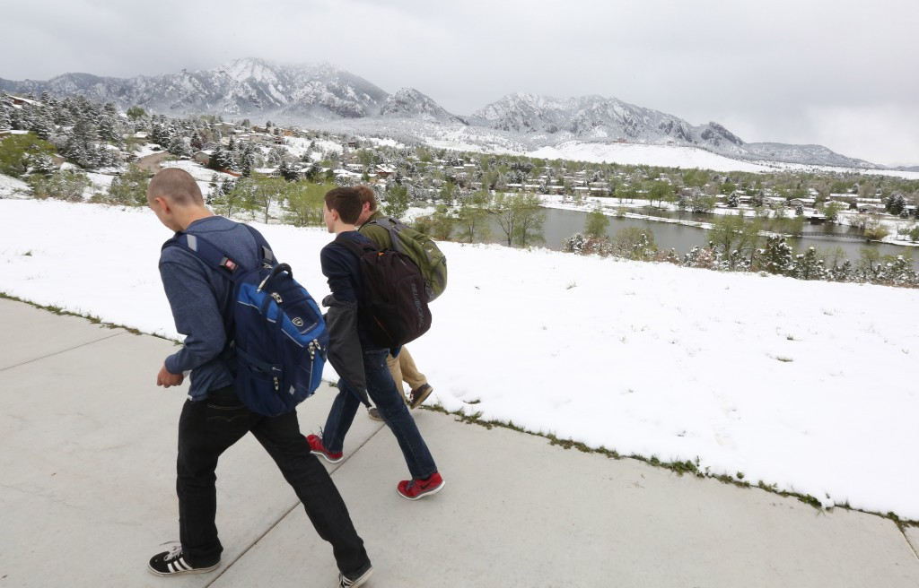 High school students walk past fresh snow from the fringe of a major spring snowstorm in the nearby mountains, in Boulder, Colo., on Monday. (AP Photo/Brennan Linsley)