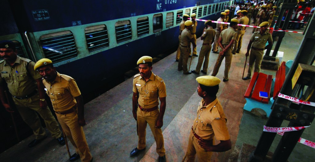Indian policemen stand guard next to a passenger train that was ripped by two blasts at the railway station in Chennai, India, Thursday (AP Photo/Arun Sankar K)