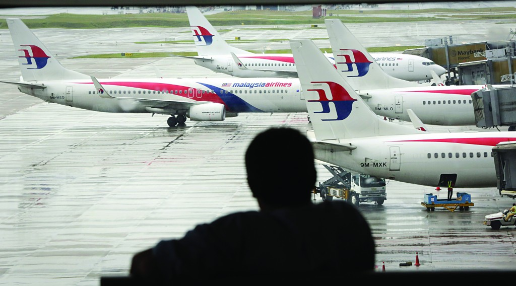 A visitor looks out from the viewing gallery as Malaysia Airlines aircraft sit on the tarmac at the Kuala Lumpur International Airport (KLIA) in Sepang, Malaysia, Tuesday (AP Photo/Vincent Thian)