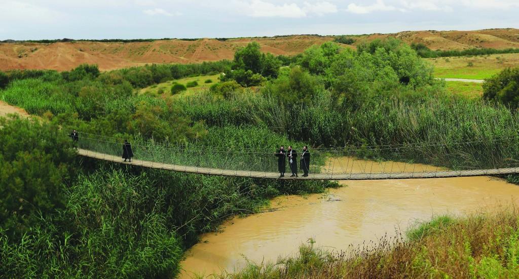Men walk on the rope bridge over the flooded Besor stream in the southern Negev desert, Israel, Thursday, May 8, 2014.  AP Photo/Tsafrir Abayov)