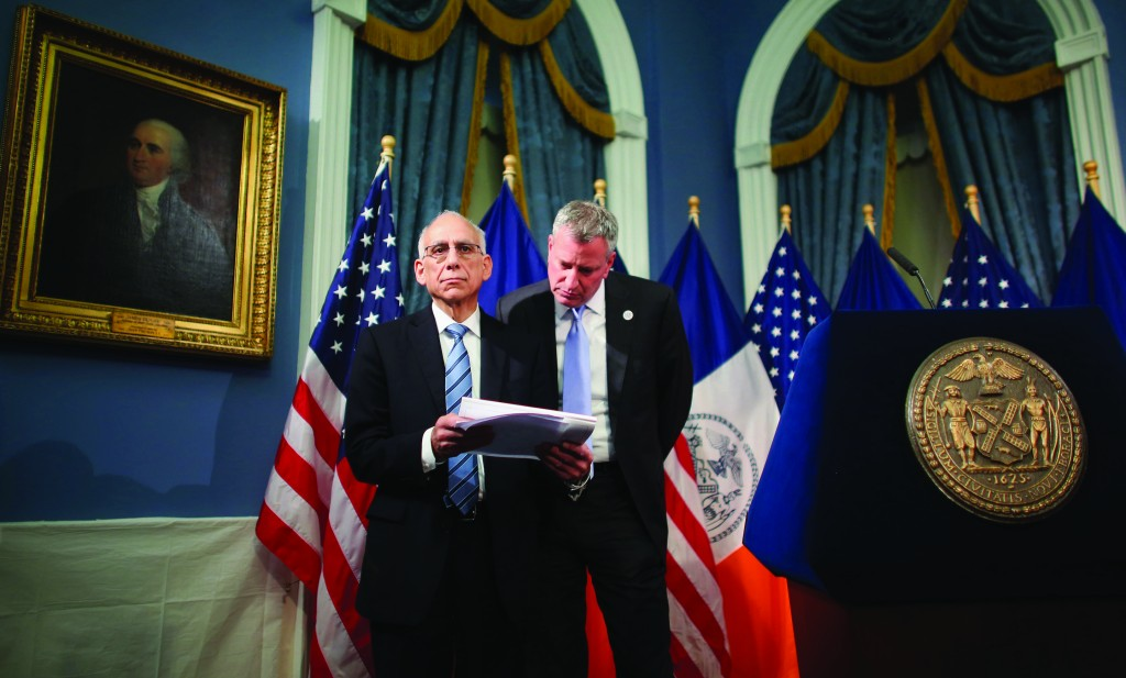 Mayor Bill de Blasio (R) on Thursday confers with city Budget Director Dean Fuleihan at City Hall. (AP Photo/New York Times, Chang W. Lee)