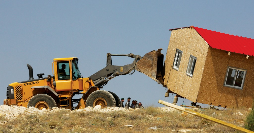 A bulldozer tears down a house during the demolition of 10 structures in the Ma'alei Rehavam outpost on Wednesday. (Nati Shohat/Flash 90)