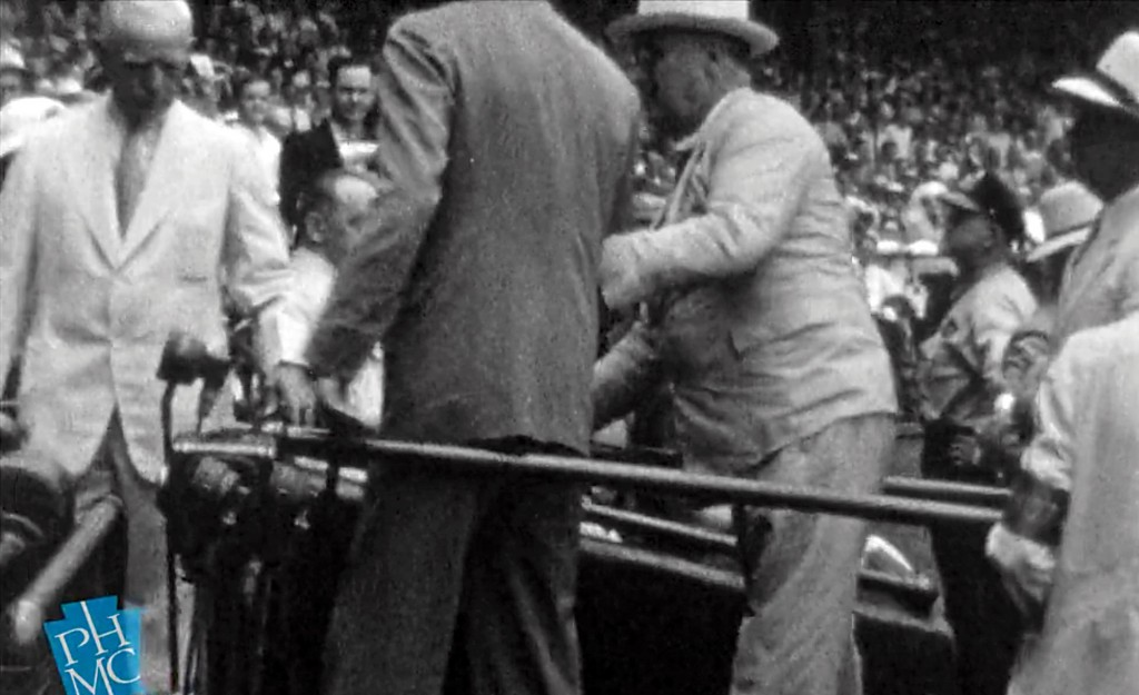 President Franklin D. Roosevelt walks with the help of an aide on July 7, 1937 at Griffith Stadium in Washington. (AP Photo/Pennsylvania Historical & Museum Commission)