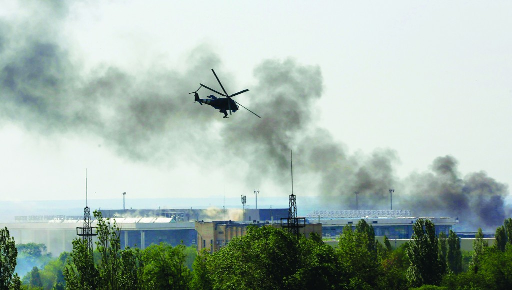 A Ukrainian helicopter Mi-24 gunship fires its cannons against rebels at the main terminal building of Donetsk international airport Monday. (REUTERS/Yannis Behrakis)