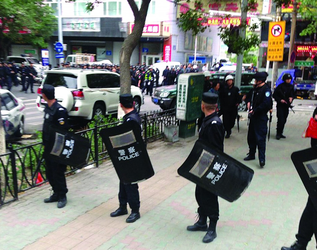 Police officers stand guard near a blast site which has been cordoned off, in downtown Urumqi, capital of northwest China's Xinjiang Uygur Autonomous Region, Thursday (AP Photo/Cao Zhiheng)