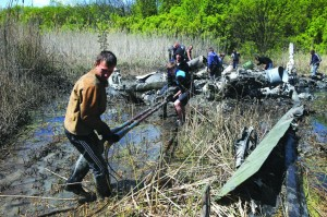 Local citizens collect parts of a downed Ukrainian military helicopter near a small town Raigorodok, outside Slovyansk, Ukraine, Tuesday. The helicopter was forced to make an emergency landing Monday during intense fighting in Slovyansk and was later destroyed by Ukrainian troops, who sought to ensure it did not fall into the hands of insurgent forces.  (AP Photo)