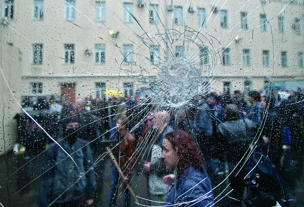 Pro-Russian protesters, seen through the cracked window of a police van, stand in the grounds of a police station in Odessa, Ukraine, on Sunday. (AP Photo/Vadim Ghirda)