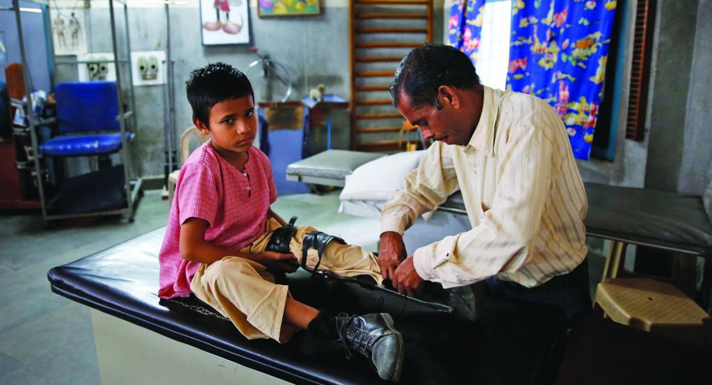 An Indian man puts an orthoses on his polio-affected boy Manish, 8, at a physical rehabilitation center in New Delhi, India  (AP Photo /Manish Swarup)