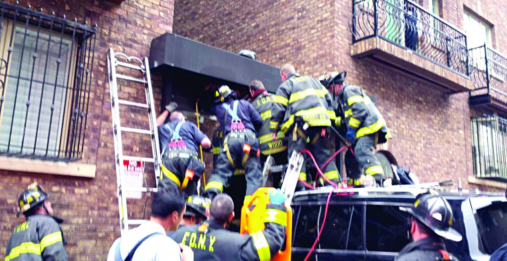 Firefighters work to free a 7-year-old boy Thursday after he got stuck on a roll-up gate in Wiliamsburg. (JDN)