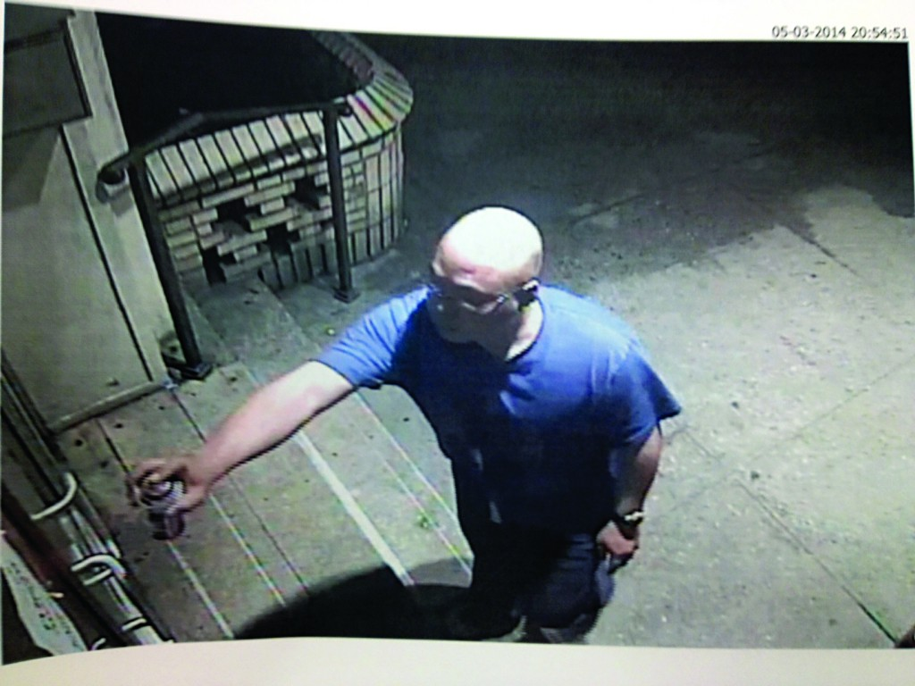 Michael Setiawan seen in a surveillance camera spray-painting a building in Boro Park on Motzoei Shabbos.