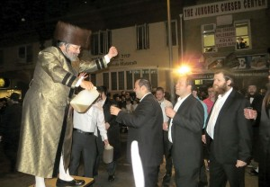 Harav Mordechai Jungreis, Nikolsburger Rebbe of Boro Park, pouring cups of oil for people to pour on the hadlakah in front of his beis medrash on Boro Park's 16th Avenue.