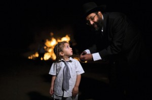 A father gives his 3-year-old son his upsherin. (REUTERS/ Amir Cohen)