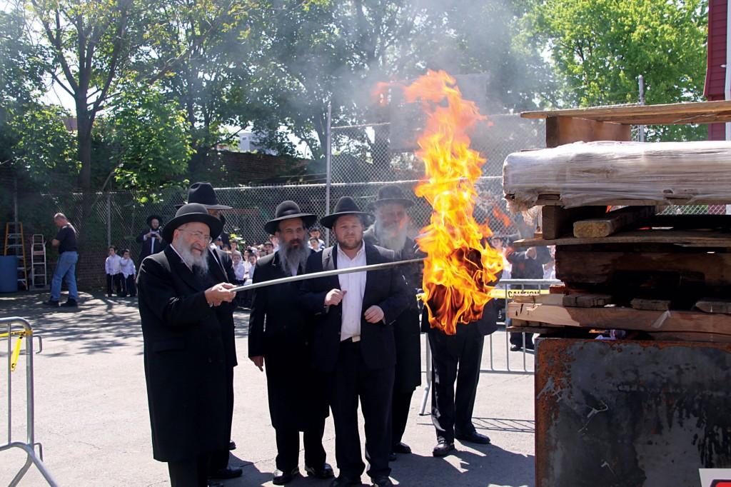 Harav Moshe Wolfson, shlita, Mashgiach of Yeshiva Torah Vodaath, lighting the bonfire in the yeshivah on Sunday morning. (Yeshiva Torah Vodaath)