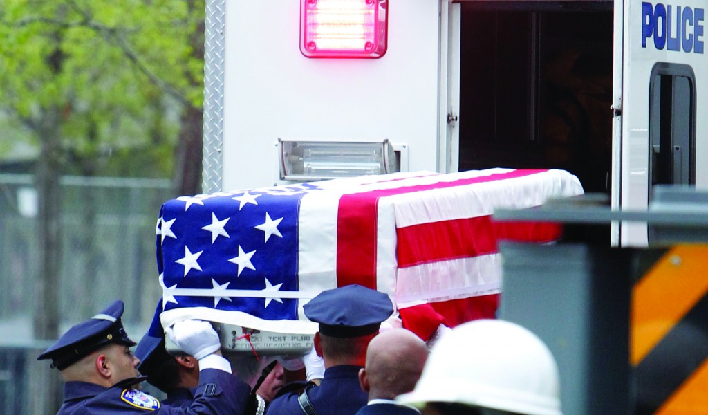 A flag-draped casket is lifted out of a police vehicle during the ceremonial transfer of unidentified remains of those killed at the World Trade Center from the Office of the Chief Medical Examiner to the World Trade Center site. (AP Photo/Jason DeCrow)