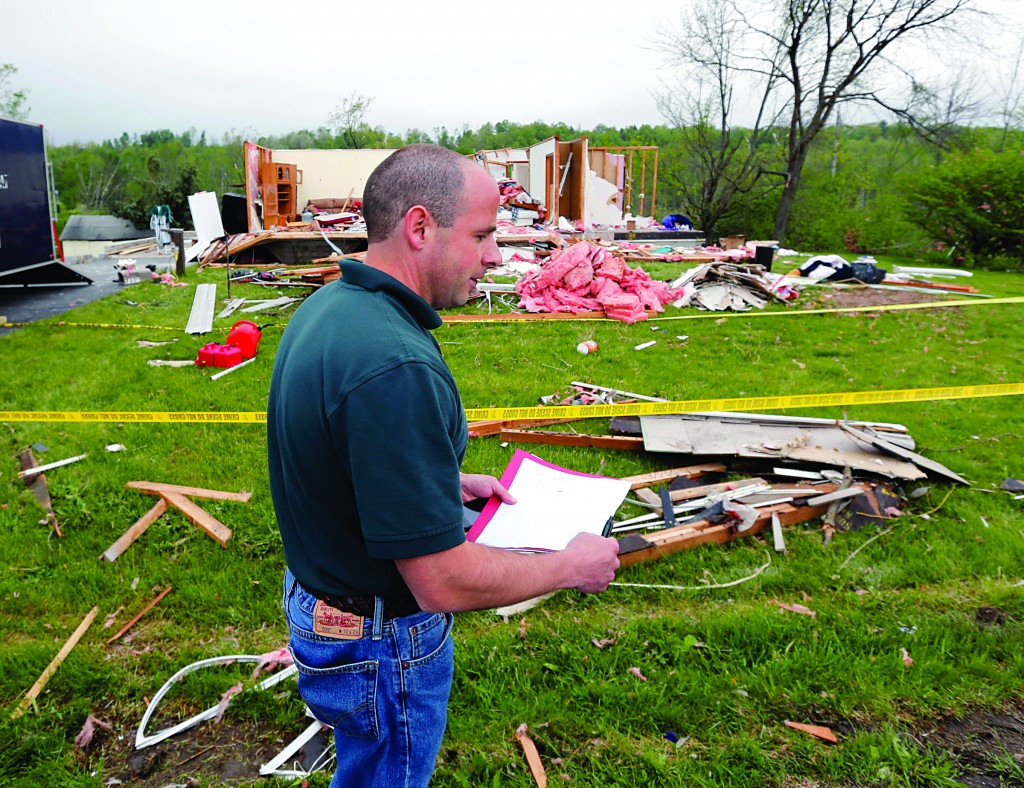 Vasil Koleci of the National Weather Service on Friday performs a storm survey in Duanesburg, N.Y. (AP Photo/Mike Groll )