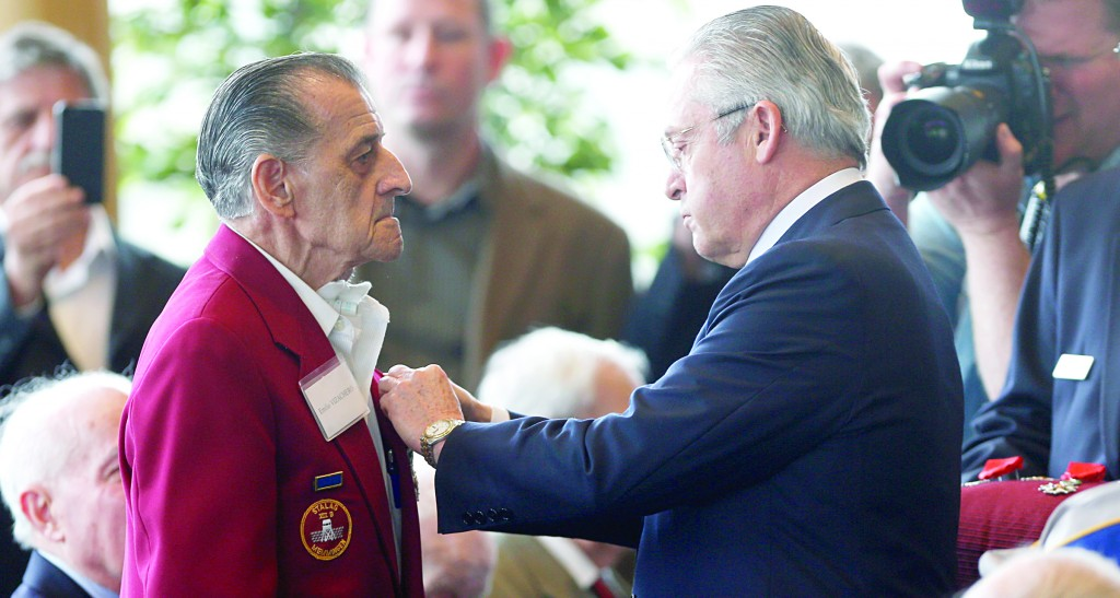 Guy Wildenstein, president of the American Society of the French Legion of Honor, on Friday presents the legion's insignia to World War II veteran Emilio Vizachero Jr., at the U.S. Military Academy in West Point, N.Y. (AP Photo/Mike Groll)